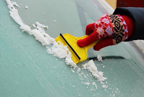 Hand der Frau Eis vom Auto-Windschutzscheibe Abschaben – Foto