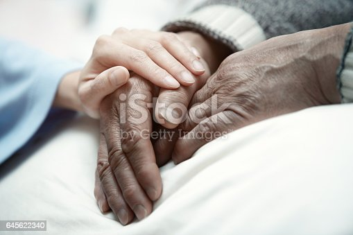 istock Hand of woman touching senior man in clinic 645622340