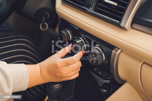 istock Hand of woman turning on car air conditioning system,Button on dashboard in car panel 1068268882