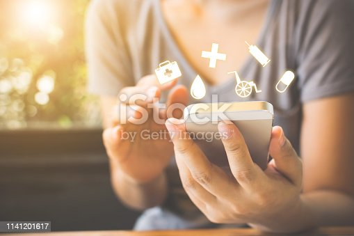 1029077176istockphoto Hand of woman using mobile phone.She is deciding to make health insurance 1141201617