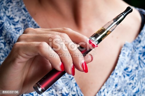 830035654istockphoto hand of woman with e-cigarette 830033136