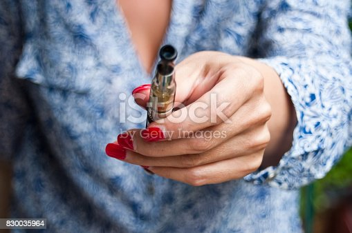 830035654istockphoto hand of woman with e-cigarette 830035964