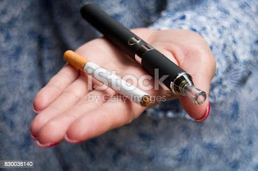 830035654 istock photo hand of woman with e-cigarette 830038140