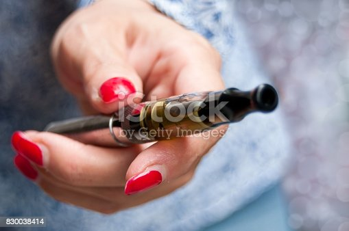830035654istockphoto hand of woman with e-cigarette 830038414