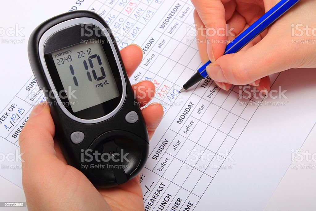 Hand of woman writing data from glucometer to medical form stock photo