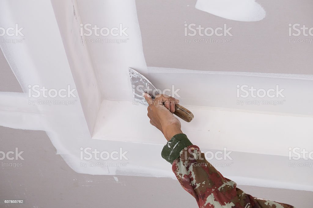 hand of worker using gypsum plaster ceiling joints - foto de acervo