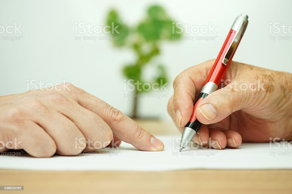 Hand of young adult pointing  elderly person where to sign stock photo