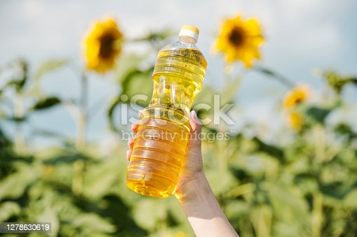 Hand of young contemporary female farmer holding plastic bottle with fresh sunflower oil against green plants with large yellow flowers