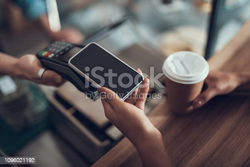Careful progressive lady with manicure holding her smartphone over the credit card payment machine while using contactless payment system