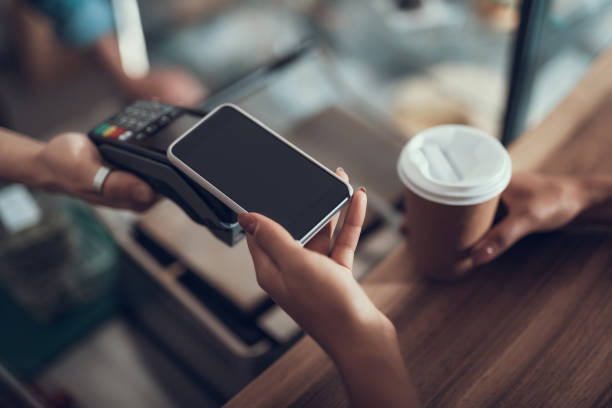 Hand of young lady placing smartphone on credit card payment machine stock photo
