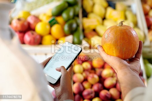 Hand of young man holding small ripe yellow pumpkin while standing by his daughter with smartphone scrolling through shopping list