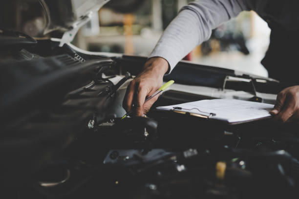 Hand of young man mechanic holding clipboard checklist the car at service center repair stock photo