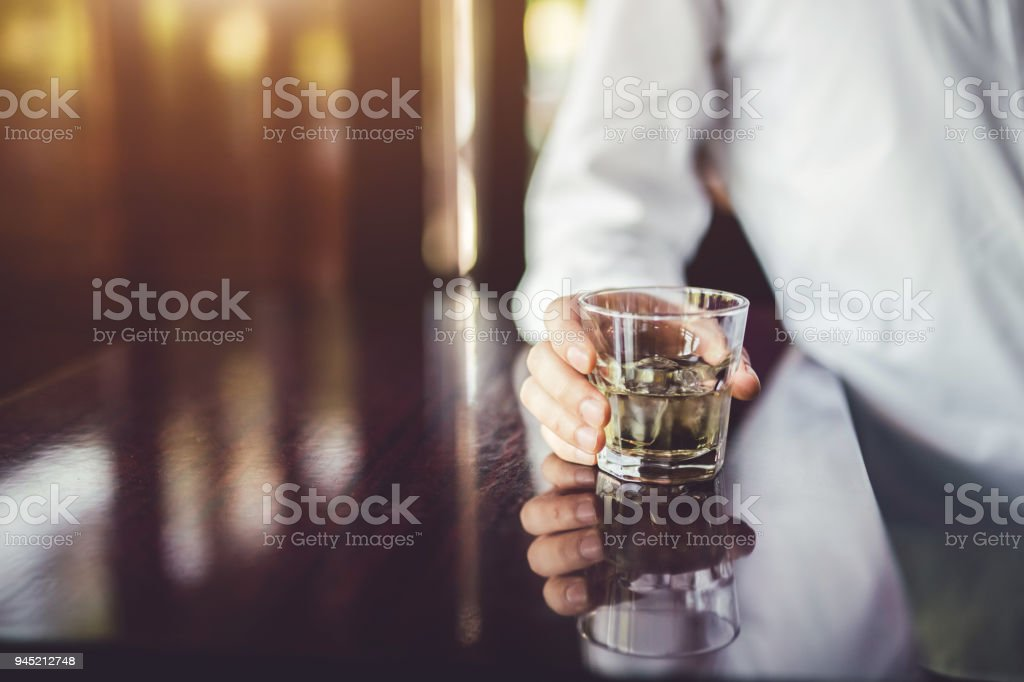 Hand of young stylish caucasian man in cafe with his favorite alcohol drink. stock photo
