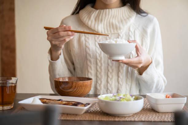 朝食を食べる若い女性の手 - ご飯茶碗 ストックフォトと画像