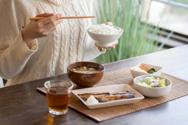 朝食を食べる若い女性の手 - 日本食 ストックフォトと画像