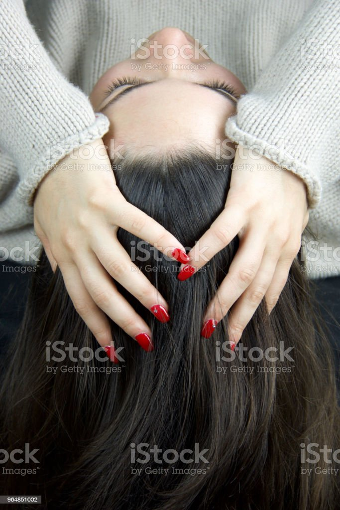 hand of  young woman with red nail polish resting on the head royalty-free stock photo