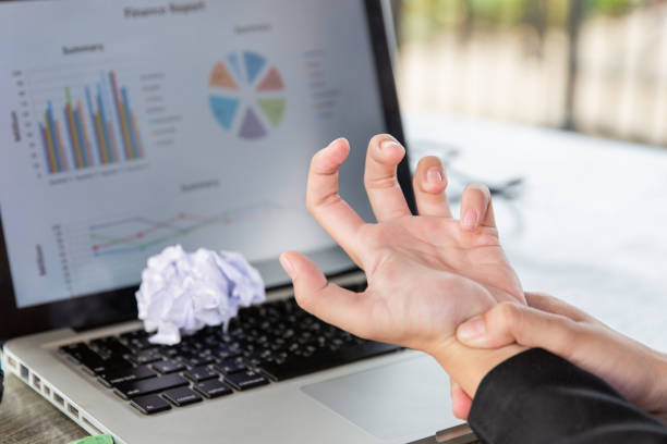 Hand of young women there is pain in the hands caused by use computer . causes his fingers to lock and he is press point pain. stock photo