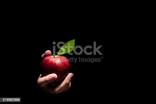 Hand offering a red apple on a black background.