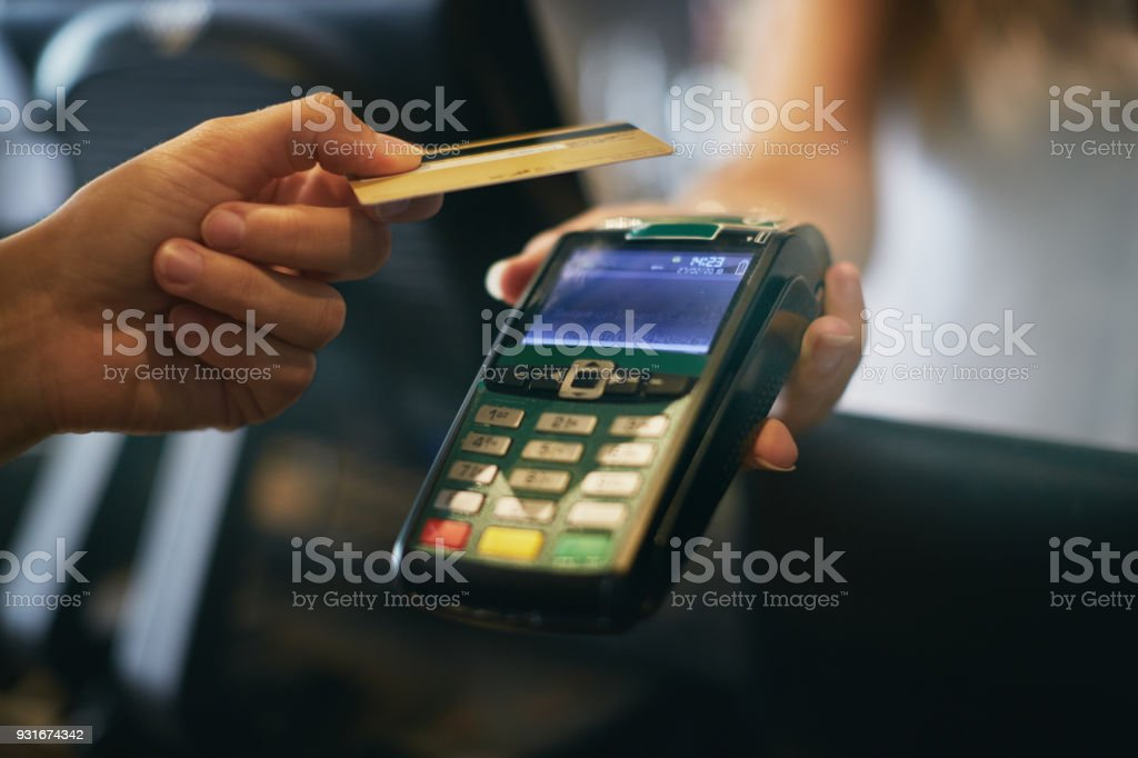 Hand offering credit card to hand-held point-of-sale device stock photo