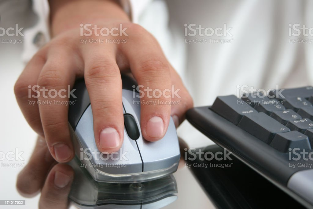 A hand on a computer mouse with keyboard nearby royalty-free stock photo