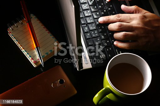 Photo of a hand on a laptop computer, cup of coffee, ballpen, notebook and a smartphone