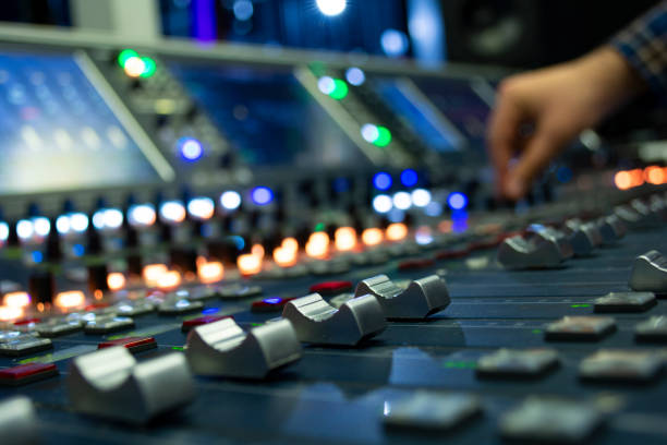 Hand on a Mixing Desk Fader in Television Gallery Hand on a Mixing Desk Fader in Television Gallery sound mixer stock pictures, royalty-free photos & images