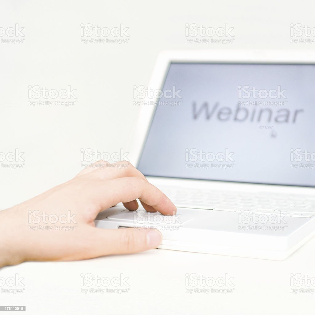 Hand on a white laptop with 'webinar' on screen stock photo