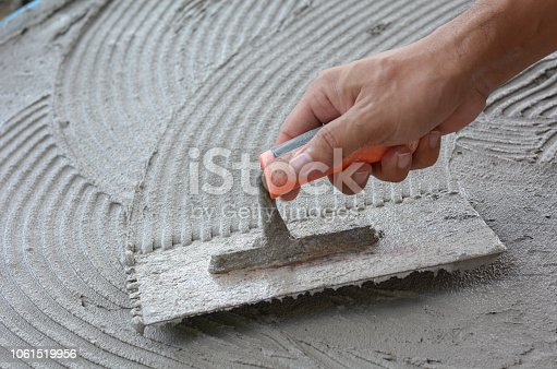 istock Hand on be bound with cement , do cement work, apply cement (over a surface) 1061519956