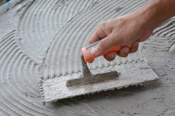 hand gebunden werden mit zement, zement-arbeit tun, gelten zement (über eine oberfläche) - diy beton stock-fotos und bilder