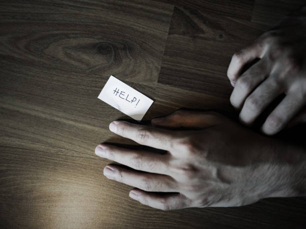 Hand on floor with help note, darkness filtered stock photo