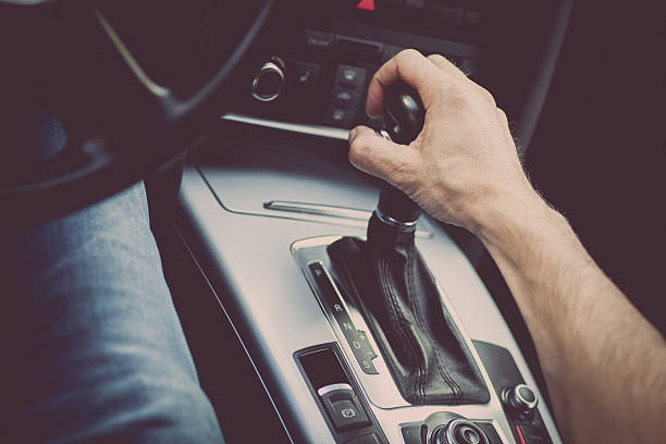 Hand on gear stick Detail of a hand pulling an automatic gear shifter in a new car. automatic stock pictures, royalty-free photos & images