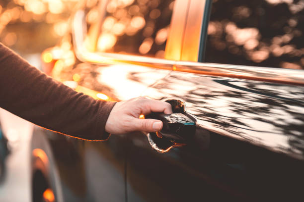 Hand on handle. Close-up of woman hand opening a car door with sunlight effect. stock photo