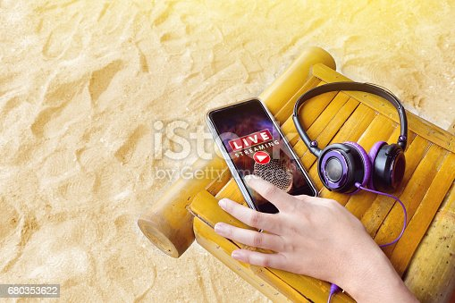 istock Hand on mobile phone with live music streaming and headphones beside on the bamboo table on the sand, music on traveling 680353622