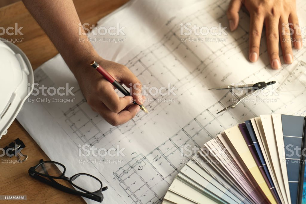 Hand on pencil of architect creative thinking in architectural design...