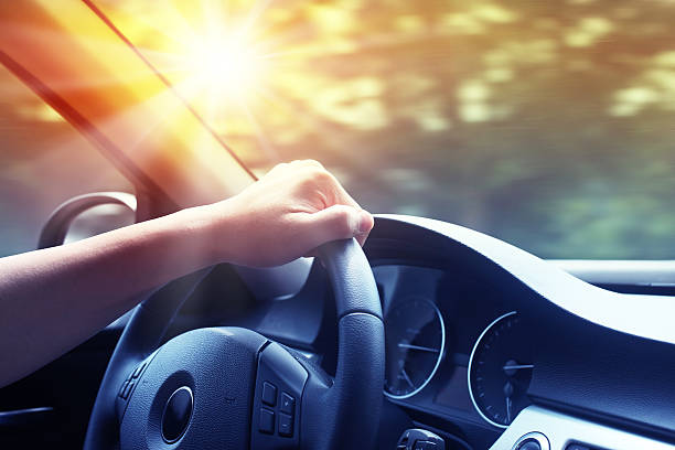 Hand on steering wheel of a car at sunset stock photo