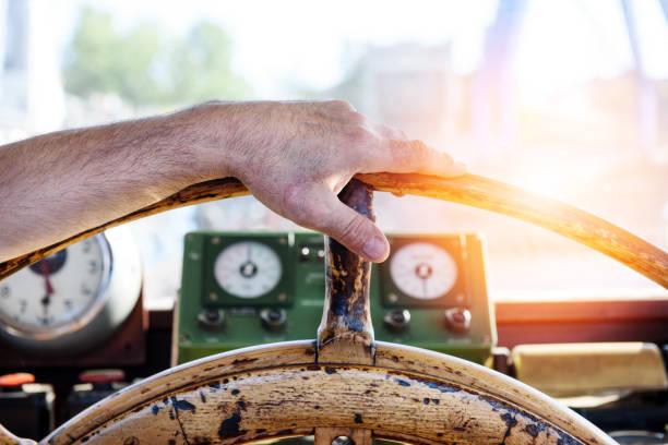 hand auf dem alten schiffsrad. sonnenuntergang auf see - rudermaschine stock-fotos und bilder