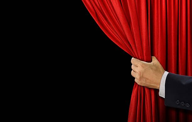 Hand open stage red curtain on black background - Photo
