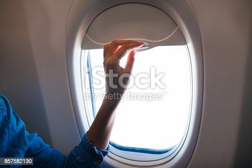 istock Hand Open the airplane window 857582130