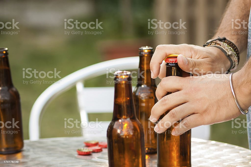 Hand opening a beer bottle stock photo