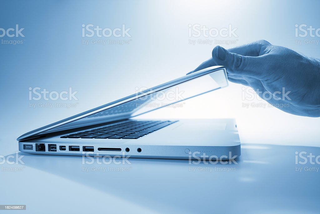 Hand opening a contemporary laptop computer royalty-free stock photo