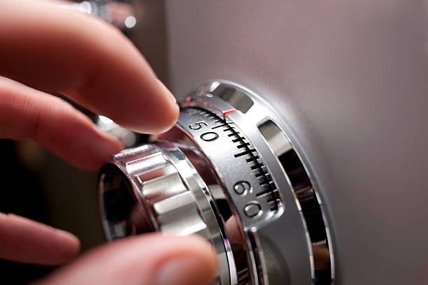 Hand opening a safe. Hand opening an office or home safe, by operating the locking dial. Shallow depth of field.  safe security equipment stock pictures, royalty-free photos & images