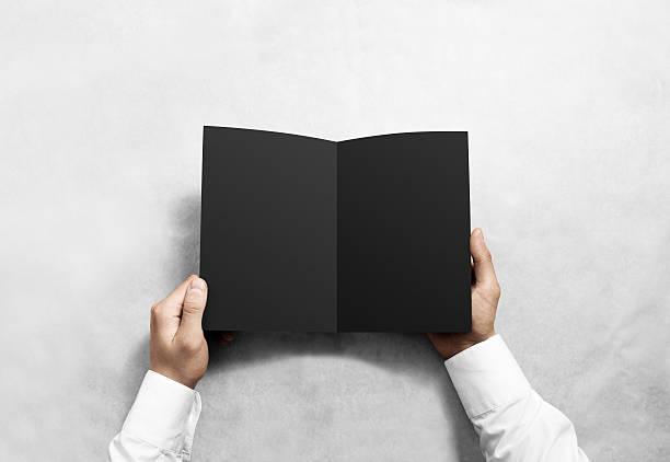 Hand opening blank black brochure booklet mockup. stock photo