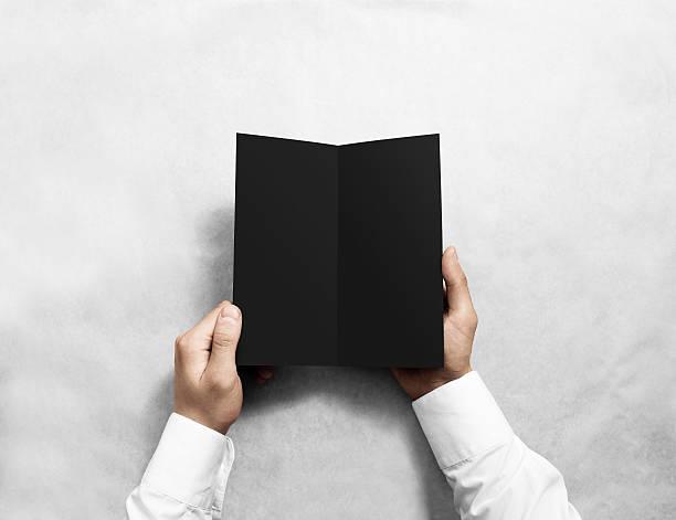 Hand opening blank black flyer brochure booklet mockup. Leaflet presentation. stock photo