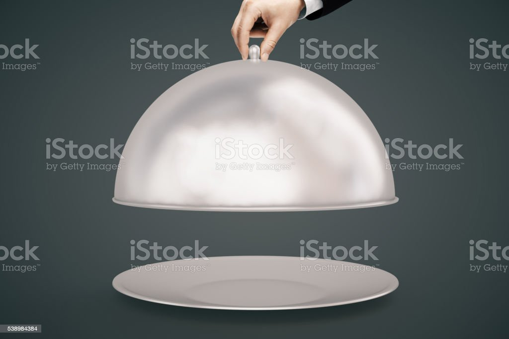 Hand opening cloche dark background stock photo