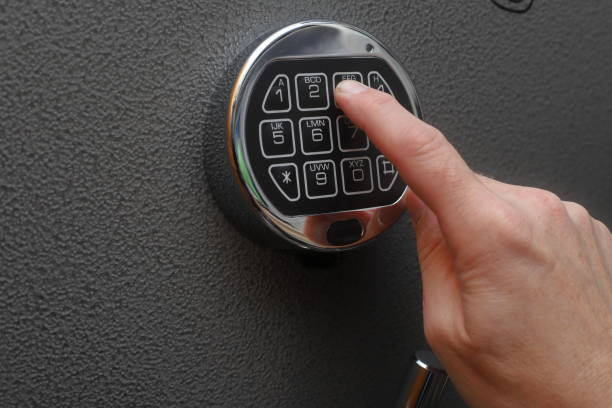 Hand opening digital lock Hand enters combination on a digital lock of a safe's door safe security equipment stock pictures, royalty-free photos & images