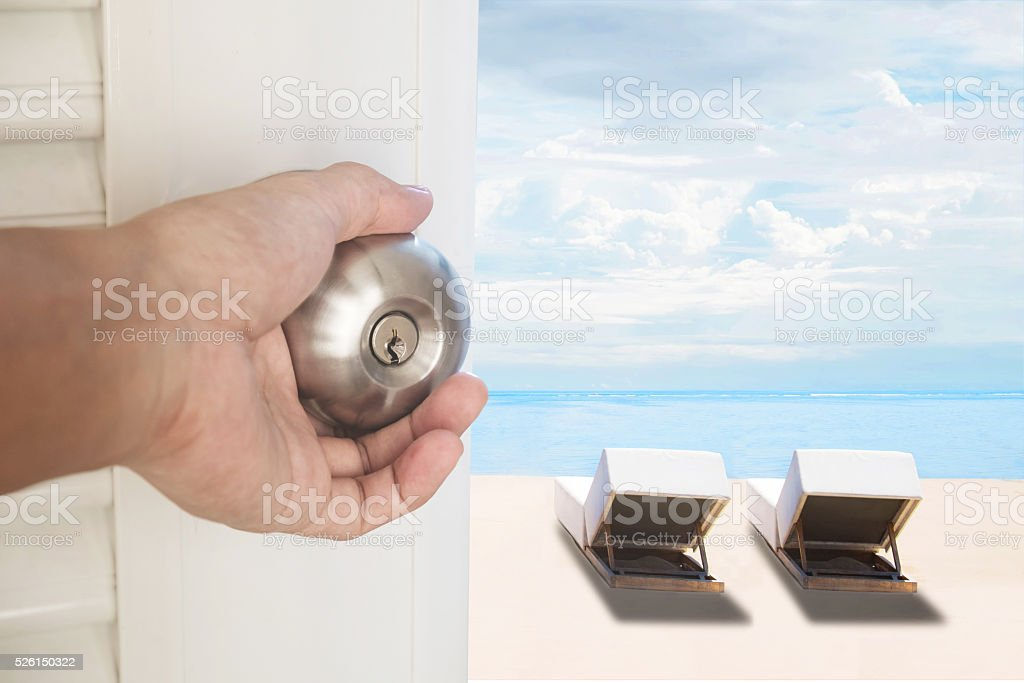 Hand opening door with the beach with chairs, vacation concepts stock photo