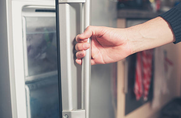 Hand opening freezer door stock photo