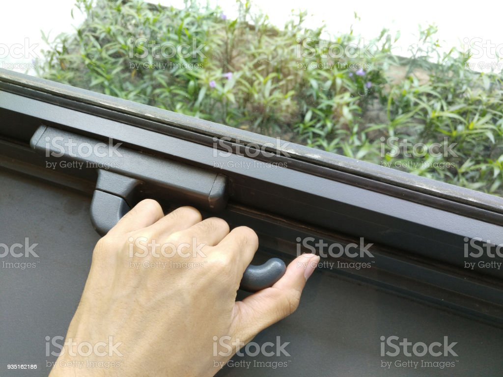 Hand opening, locking window securely, to protect from unwanted things like insects, bugs, fly, birds, pollution (noise, gas, water), unknown person. (Lock and open Concept, cannot come in, be alone) stock photo