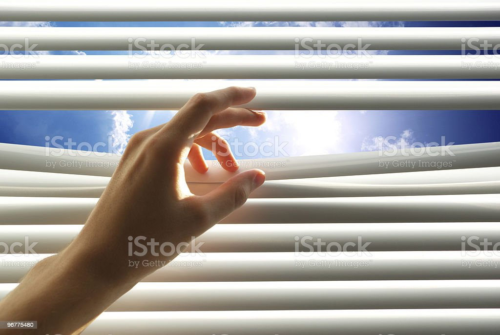 Hand opening the jalousie with fingers with bright sky view royalty-free stock photo