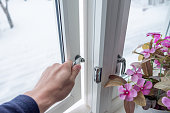 Hand opening window with flower decoration in winter
